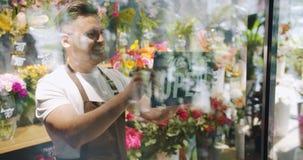 Cámara lenta del propietario de negocio que pone en nosotros somos muestra abierta en puerta de la floristería almacen de metraje de vídeo