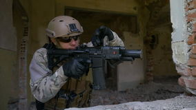 Cámara lenta del soldado de las fuerzas especiales que defiende el edificio que sostiene su arma fuera de la ventana almacen de metraje de vídeo