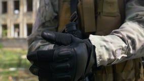 Cámara lenta del soldado que aprieta sus guantes militares para mejor sostener su arma del rápido y prepararse para tirar almacen de video
