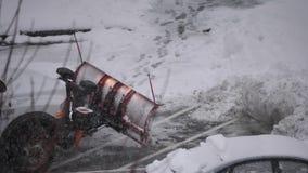 Cámara lenta del tractor compacto con la nieve que ara el estacionamiento de limpieza del equipo