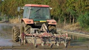 Cámara lenta del tractor que ara el campo del arroz Granjero con la máquina de la máquina segador metrajes