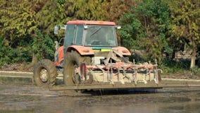 Cámara lenta del tractor que ara un campo del arroz en campo en Tainan, Taiwán metrajes
