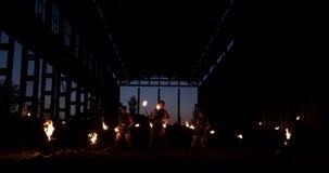 Cámara lenta: Demostración del fuego en el artista de sexo femenino de la demostración tres del hangar y un hombre con los lanzal metrajes
