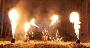 Cámara lenta: Demostración del fuego en el artista de sexo femenino de la demostración tres del hangar y un hombre con los lanzal almacen de metraje de vídeo