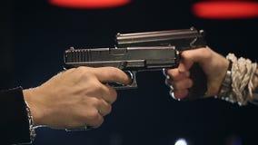 CÁMARA LENTA: Dos manos masculinas con la toma de los armas se tienen como objetivo almacen de metraje de vídeo