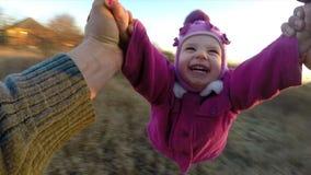 Cámara lenta. El hombre gira a su pequeña hija al aire libre, primer Person View From almacen de metraje de vídeo
