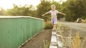 Cámara lenta: El niño pequeño camina en el encintado del camino almacen de video