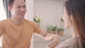 Cámara lenta - el rato asiático de la danza de los pares escucha la música en sala de estar en casa almacen de video