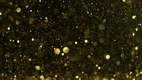 Cámara lenta estupenda de partículas de oro que brillan en fondo negro almacen de metraje de vídeo