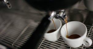 Cámara lenta estupenda del café caliente del café express que vierte en las tazas de una porcelana de dos blancos de la máquina d almacen de metraje de vídeo