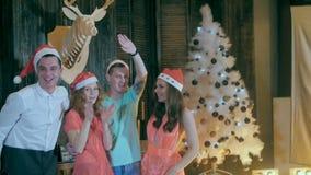 Cámara lenta Grupo feliz de amigos en una fiesta de Navidad que se divierte, sonriendo en cámara celebrando Nochebuena almacen de metraje de vídeo