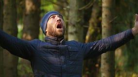Cámara lenta hombre barbudo del viajero que grita en alta voz aumentando sus manos para arriba metrajes