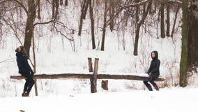 Cámara lenta, hombre de los pares y paseo de la mujer en el oscilación hecho en casa en bosque nevoso almacen de metraje de vídeo