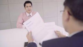 Cámara lenta - hombre de negocios asiático joven atractivo en una entrevista de trabajo con el encargado corporativo de los perso almacen de video