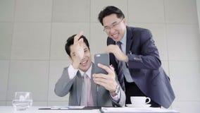 Cámara lenta - hombre de negocios usando el smartphone para comprobar datos del mercado de acción Varón que comprueba las cartas  metrajes