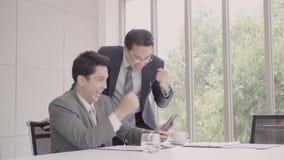 Cámara lenta - hombres de negocios hermosos elegantes usando el smartphone para comprobar datos del mercado de acción almacen de video