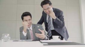 Cámara lenta - hombres de negocios hermosos elegantes usando el smartphone para comprobar datos del mercado de acción