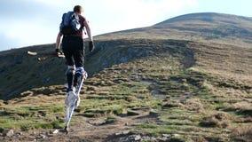 cámara lenta 4k - el hombre en los zancos entra a la montaña almacen de metraje de vídeo