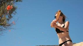 Cámara lenta: La chica joven atractiva en un traje de baño negro y vidrios, destruye las frutas y verduras con un bate de béisbol metrajes