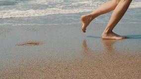 CÁMARA LENTA: los pies de la mujer que corren en la playa soleada caliente de la arena almacen de video