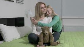 A cámara lenta - mamá rubia hermosa y su hija linda que abrazan con amor almacen de metraje de vídeo