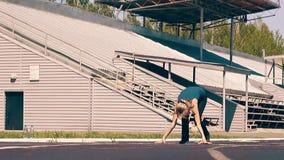 Cámara lenta: Muchacha linda joven, constitución deportiva, en el estadio Ella se coloca en el comienzo, después el funcionamient metrajes