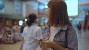 Cámara lenta - mujer asiática feliz que usa la carretilla o el carro con mucha el equipaje que camina en pasillo terminal almacen de metraje de vídeo