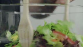 Cámara lenta - mujer joven consciente de la salud principal que lanza una ensalada verde orgánica sabrosa almacen de video
