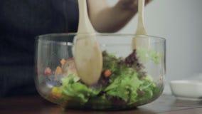 Cámara lenta - mujer joven consciente de la salud principal que lanza una ensalada verde orgánica sabrosa almacen de metraje de vídeo