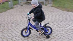 Cámara lenta Niño pequeño en un sombrero gris y una chaqueta caliente que montan una bicicleta azul en el patio almacen de video