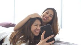 Cámara lenta - par feliz lesbiano asiático joven hermoso de las mujeres LGBT que se sienta en abrazo de la cama y que usa el telé metrajes