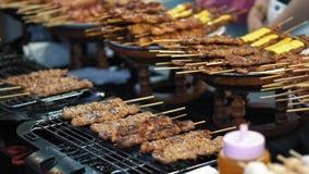 Cámara lenta, preparando pequeños kebabs deliciosos en la parrilla caliente Mercado callejero tradicional de la comida en Tailand almacen de metraje de vídeo