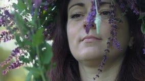 Cámara lenta, primer, muchacha hermosa con una guirnalda en el jefe de los colores del control de las flores de los acianos del c almacen de video