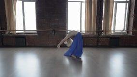 C?mara lenta que sorprende - el bailar?n rubio en falda azul hace la rueda en el estudio metrajes
