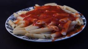 Cámara lenta, salsa de colada del marinara sobre los espaguetis Pastas cocinadas del penne con mantequilla y queso y albahaca en  almacen de video