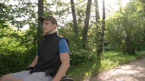 A cámara lenta siga de hombre joven discapacitado del estudiante en una silla de ruedas observando la naturaleza alrededor de él, metrajes