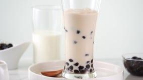 Cámara lenta - té de colada de la leche en la taza de cristal con la burbuja popular sabrosa de la perla de la tapioca de Taiwán  almacen de metraje de vídeo