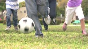 Cámara lenta tirada de la familia hispánica que juega al fútbol junto almacen de metraje de vídeo