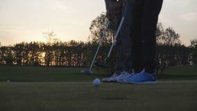 Cámara lenta tirada de los golfistas que ponen la bola en verde metrajes