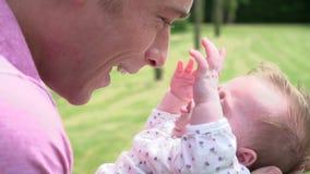 Cámara lenta tirada del padre Holding Baby Daughter en jardín almacen de metraje de vídeo