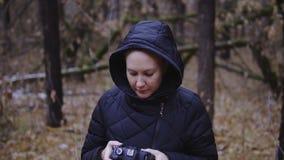 Cámara lenta, tiro cinemático la muchacha está caminando en el bosque del otoño con una cámara de la foto fotografía la naturalez almacen de metraje de vídeo
