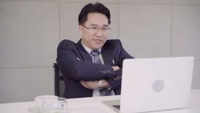 Cámara lenta - traje que lleva del asiático del hombre de negocios acertado del CEO que trabaja con el ordenador portátil en el e
