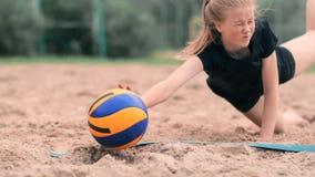 Cámara lenta: una mujer joven que salta en la caída golpea la bola en la arena El jugador de voleibol hace a un equipo y juega almacen de video