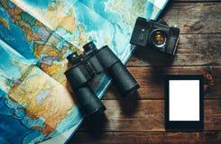 Cámara, mapa, tableta y prismáticos de la película del vintage en la tabla de madera, visión superior Explorador Journey Concept  imágenes de archivo libres de regalías