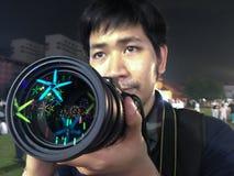 Cámara masculina de la tenencia de la mano que tiene reflejar la luz hermosa en la lente fotografía de archivo
