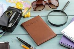 Cámara, pasaporte, mapa y cáscaras del concepto del viaje en una tabla de madera azul Relajación holidays fotografía de archivo