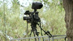 Cámara profesional del cine fijada en el ambiente al aire libre almacen de video