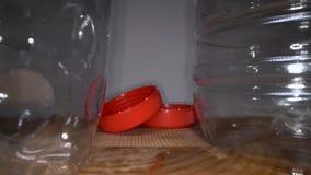 Cámara que resbala las botellas plásticas vacías del canal con las cápsulas en fondo de madera Basura pl?stica transparente, reut almacen de metraje de vídeo