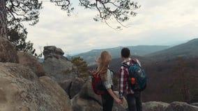 Cámara que se mueve hacia los adolescentes jovenes en amor, llevando a cabo sus manos y situación en el top de la alta montaña Él almacen de video
