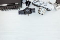 Cámara retra de la foto y carretes de película negativos en el backg de madera blanco Fotografía de archivo